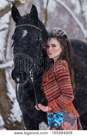 Native indian woman with traditional makeup and hairstyle in snowy winter. Beautiful girl in ethnic dress in the forest hugging a horse