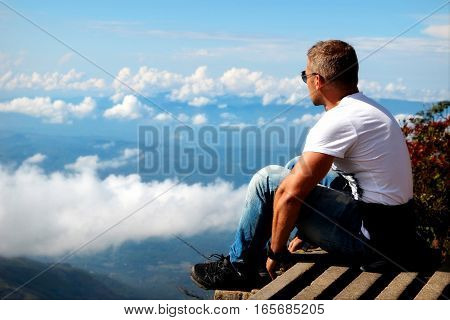 Man relaxes on the edge of the cliff . Plateau