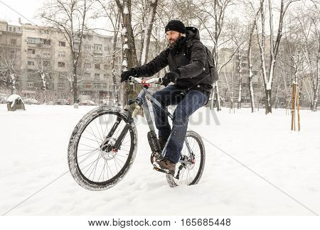 A man rides a bicycle in snowy weather