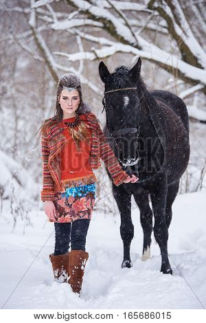 Native indian woman with traditional makeup and hairstyle in snowy winter. Beautiful girl in ethnic dress in the forest with a horse