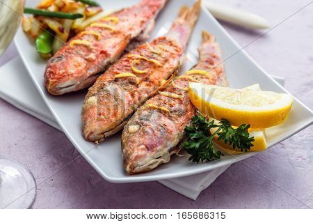 Plate of fried small fish red mullet and lemon, close view.