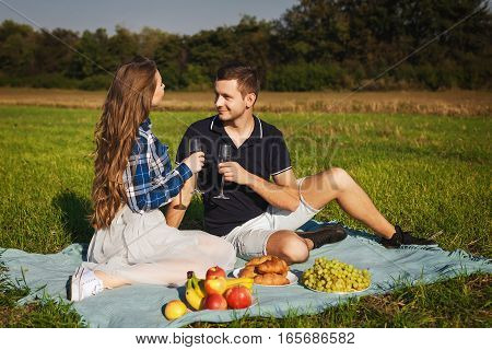Man and woman drinking wine at a picnic. They look at each other and smiling