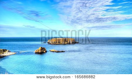 Dangerous cliff rocks rises from the sea. High Definition Photo of dangerous cliff rocks rising from a deep blue sea. Clear azure skyline lasts to the horizon. Still sea waters reflect few clouds from the sky.