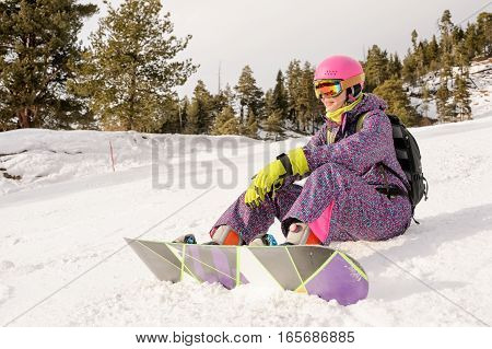 girl sitting on the ski slopes in winter time