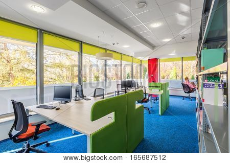 Colorful library interior with wood desks with green partitions