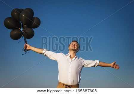 happy guy in white shirt with black balloons reaches for the sky and smiling