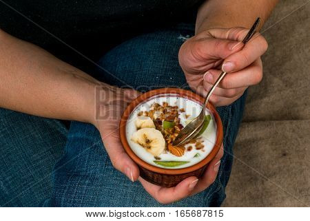 iet concept. Plus size (fat) girl eating diet and healthy breakfast: homemade yogurt with golden granola with nuts and fresh fruit (kiwi and banana)