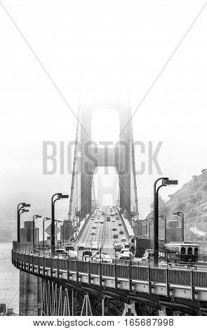 Golden Gate Bridge in fog with traffic.