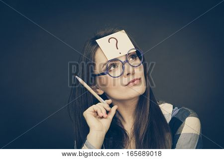 Woman confused thinking seeks a solution paper card with question mark on her head. Doubtful young female in glasses studio shot on black