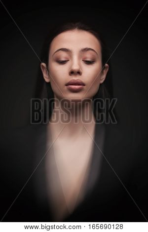 portrait young elegant woman with closed eyes wearind black jacket. Fashion studio shot. Motion effect
