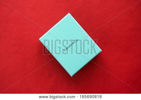 DUBAI, United Arab Emirates - 2 JANUARY 2017: Signature Tiffany Blue Box - brand package of luxury jewelry brand Tiffany and Co. on the red velvet background, Dubai, UAE, 2 January 2017