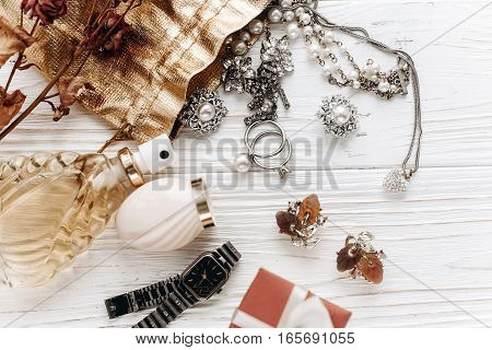 Luxury Expensive Jewelry Rings Earrings And Perfume And Watch On White Rustic Wooden Table With Spac