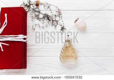Luxury Expensive Jewelry And Perfume And Stylish Red Present Flat Lay On White Rustic Wooden Backgro