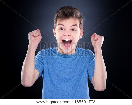 Half-length emotional portrait of caucasian teen boy. Victory screaming teenager wearing blue t-shirt on black background. Funny winner child shouting with his hands up.