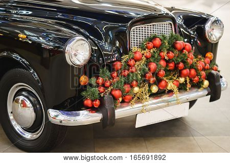 black vintage car decorated with Christmas tree and balls