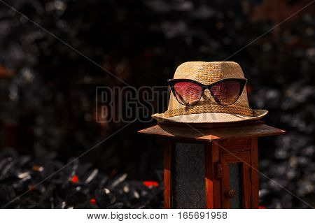 The photobackgroundtexture of the straw white hat with red glassesspectacles on the lamp in cold tone and cold temperature with red flowers into wild nature