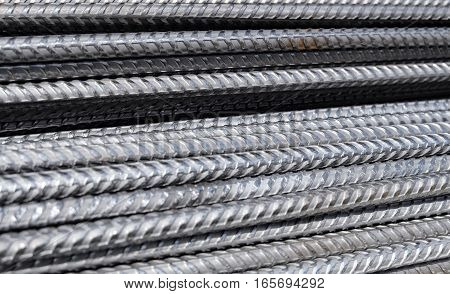 A closeup of a pile of division rebar from a construction site. The ribbed metal bars are to be used as reinforcement / armature in concrete. The steel rods are stacked horizontally.