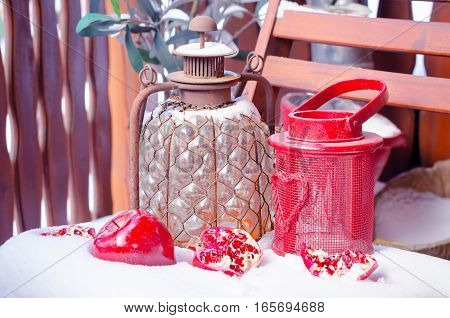 Cozy Scene with Vintage Oil Lamp and Candle Lamp, Heart on the Snow, Pomegranate, Outdoors. Copy space, Selective focus, Natural Decoration