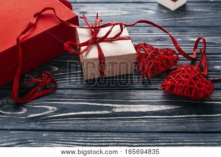 Stylish Red Craft Present And Two Heart Ribbons On Black Rustic Wooden Background. Happy Valentines