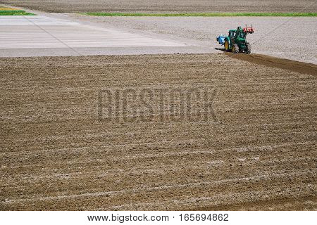 Image of Tractor in a Plowed Field