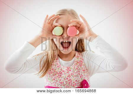 Beautiful young cheerful woman holding macaroons on her eyes and joking.