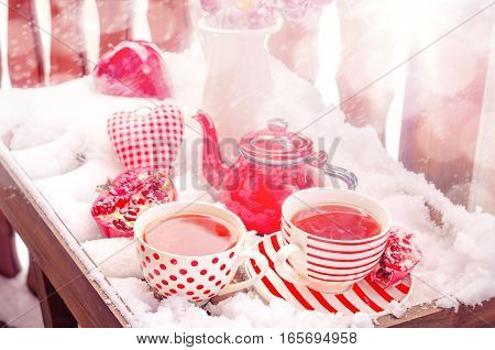 Cozy Scene with Vintage Heart, Hot Cup of Tea on the Snow, Red Teapot, Pomegranate, Copy space, Selective focus, Toned.