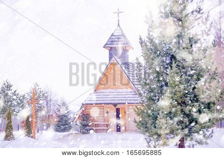 Winter snowy landscape with a mountain church. Nature scene with snow and sun flare, sunlight, daylight, outdoors. Abstract blurred background. Copy space, Selective focus, toned.