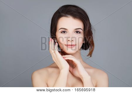 Spa Model Woman with Healthy Skin and Natural Makeup on Gray Background. Skincare Concept