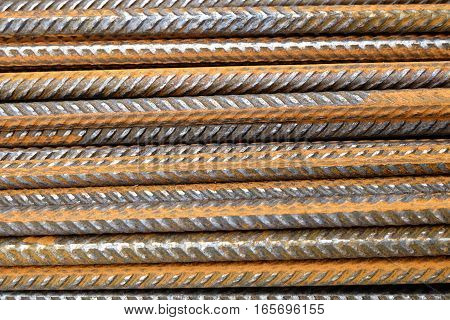 A closeup of a pile of rusty division rebar on an industrial building construction site. The deformed reinforcement bars are horizontally stacked and corroding. Even rusting they are still usable as armature in cement.