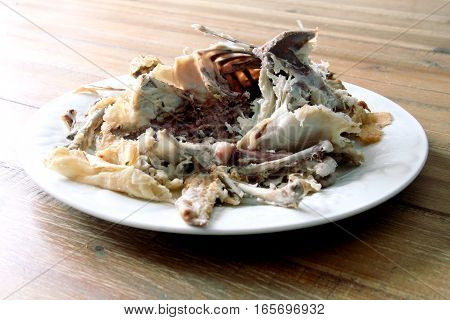Roast Chicken Carcass Remains On A Plate On A Wooden Table