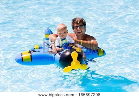 Young active father playing with cute baby happy laughing boy sitting on inflatable toy airplane with water gun enjoying hot summer day in an outdoor pool of a tropical resort during vacation.