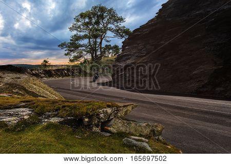 Biker sweep spin on his motorbike around rocks. Mountain landscape