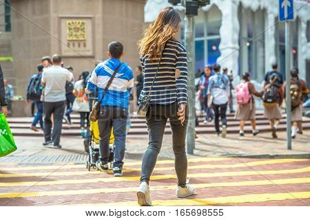Hong Kong, China - December 6, 2016: Asian girl walking with her mobile phone in hand along the intersection of Times Square, largest shopping mall in Causeway Bay, the luxury shopping district.