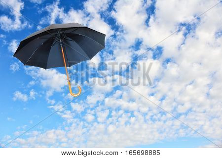 Wind of change concept.Black umbrella flies in sky against of pure white clouds.Mary Poppins Umbrella.