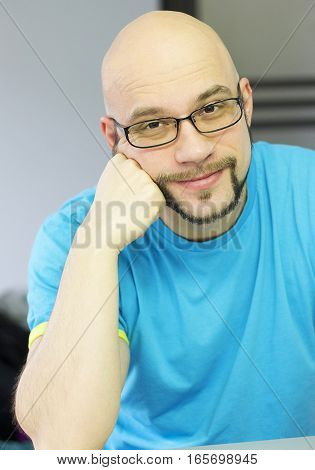 Kind bald man with stylish beard and glasses smiling kindly.