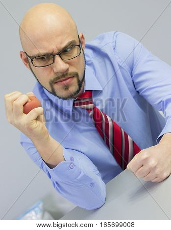 Angry boss squeezing stress ball in the office.