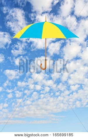 Wind of change concept.Umbrella in Ukrainian flag colors flies in sky against of white clouds. Mary Poppins Umbrella.