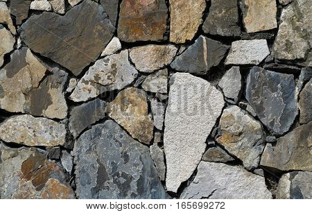 A stone wall made of different colored stones. Through the irregular shapes and the precise fitting the pattern resembles a mosaic.