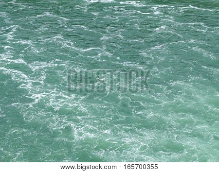 Clean water surface with emerald color tone. The river carries light but very foamy waves from the impact of a waterfall, looking like a white marble pattern on green backround.