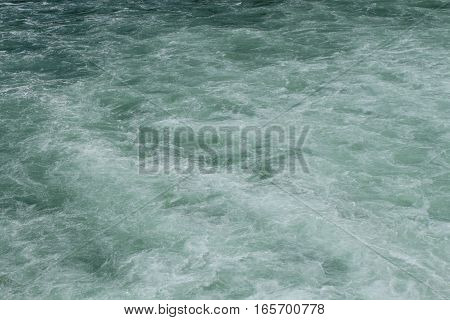 Water flowing down a river. The color tone is green, resembling an emerald. The waves are light but foamy from the impact of the waterfall it just passed.