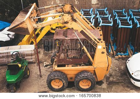 Small yellow forklift loader in the parking lot for machinery