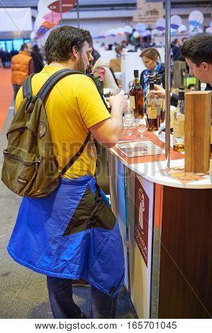 STRASBOURG FRANCE - FEB 22 2016: Man tasting French cognack on French wine market