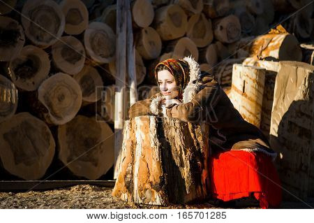 Beautiful woman in a sheepskin coat and scarf sits leaning on a log on the background of large logs. Russian national color.