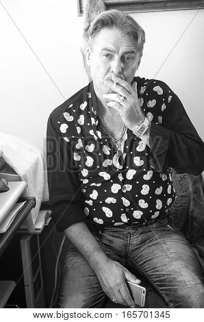 adult man smokes a cigarette sitting, business wealthy, aged, male portrait bw