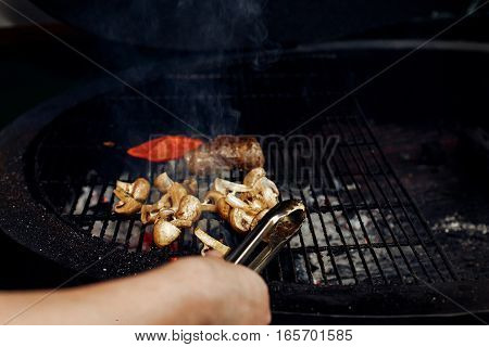 Vegetables And Meat Grilling.  Hand With Tongs And Beefsteak Mushrooms  Tomatos Garlic On Grill. Cat