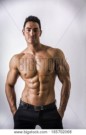 Handsome shirtless muscular man with elegant pants, standing, on light background