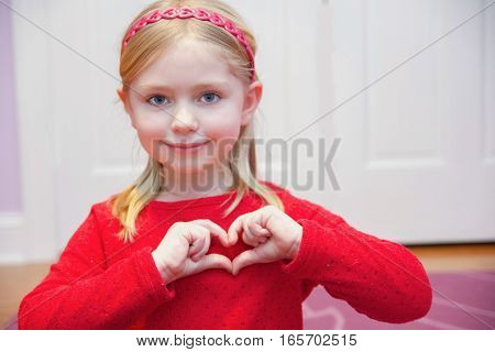 adorable school age girl making shape of heart with hands for valentine's day