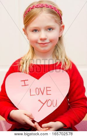 adorable school age girl holding i love you sign for valentine's day