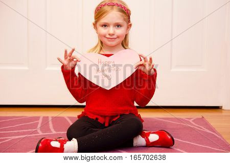 adorable school age girl wearing red and holding happy valentine's day sign