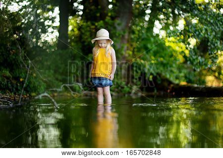 Cute Little Girl Having Fun By A River On Sunny Summer Day